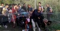 Migrants break past security fence near refugee camp in Europe.