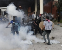 Police react after a demonstrator threw back a tear gas canister during a demonstration next to the city of Miami Police Department on Saturday, May 30, 2020
