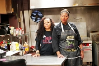 In this March 24, 2020, photo, Keisha Henry, right, and her business partner Erica Norwood pose for a portrait inside their lounge and catering business in New Orleans. Henry said she lost about $10,000 in revenue last week after three big functions she was slated to cater ended up canceling. Meanwhile, she still has expenses related to launching a bar and lounge six months ago. Henry said she regrettably had to lay off several employees.